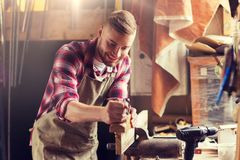 Carpenter working with plane and wood at workshop. Profession, people, carpentry, woodwork and people concept - happy carpenter with jointer planing wood plank Stock Photos