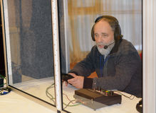 Profession. Translator at work. Translator at work. Sitting in a booth with headphones and microphone Stock Images