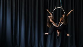 Professional acrobats performs a gymnastic trick on the aerial hoop stock video