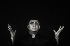 A professional actor in the guise of a priest against a dark background Royalty Free Stock Photo