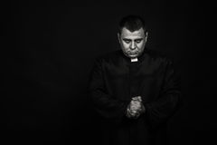 A professional actor in the guise of a priest against a dark background Royalty Free Stock Images