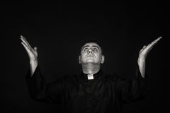 A professional actor in the guise of a priest against a dark background Royalty Free Stock Image