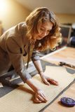 Professional adult female tailor marking cloth pattern with chalk at sewing workshop and looking at camera stock photos