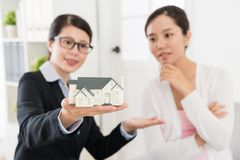 Advisor woman and investor looking at house model. Professional advisor women and investor lady looking at house model discussing building construction design Royalty Free Stock Image