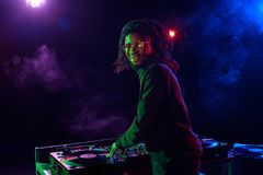 Professional african american club DJ with sound mixer. In nightclub stock photography