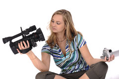 Professional or amateur. Young pretty woman with professional and amateur videocameras royalty free stock photography