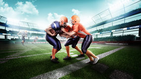 Professional american football player in action on stadium. Young and strong american football players in the action on stadium on green grass Royalty Free Stock Photos