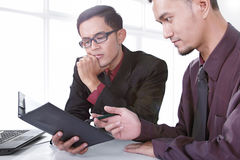 Professional analysts discussing a business report Stock Photos