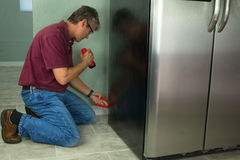 A professional appliance repair service technician man repairing Stock Images