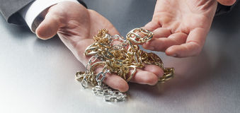 Professional appraiser showing golden necklaces in hands. Appraising jewels and precious metals for work or welath in manager's hands royalty free stock photography