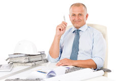Professional architect with blueprint behind table Stock Images
