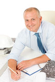 Professional architect with blueprint behind table Stock Photography