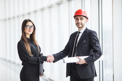 Professional architect and businesswoman handshake against panoramic window in office. Stock Image