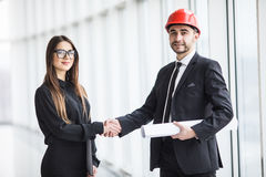 Professional architect and businesswoman handshake against panoramic window in office. Royalty Free Stock Images