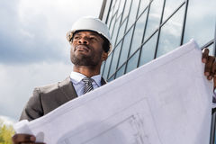 Professional architect in hard hat holding blueprint outside modern building Stock Images