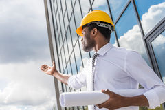 Professional architect in hard hat holding blueprint outside modern building Royalty Free Stock Photo
