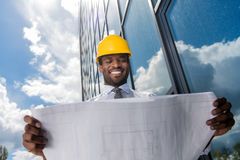 Professional architect in hard hat holding blueprint outside modern building Royalty Free Stock Image