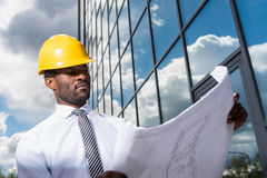 Professional architect in hard hat holding blueprint outside modern building Royalty Free Stock Photos