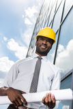 Professional architect in hard hat holding blueprint outside modern building Stock Image