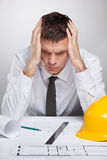 Professional architect holding head and reading. Stock Photo