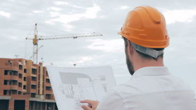 Professional Architect looking at blueprints at a building site. stock video footage