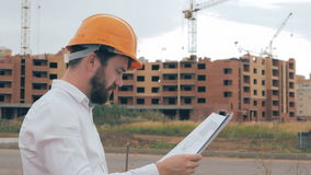 Professional Architect looking at blueprints at a building site. stock footage