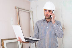 Professional architect talking on the mobile phone with laptop i Stock Image