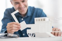 Professional architect working at office desk, he is assembling an architectural model, design and architecture concept stock images