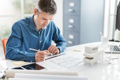 Professional architect working at office desk, he is drawing and making measurements on a project blueprint, design and stock photography