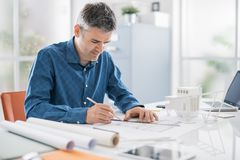 Professional architect working at office desk, he is drawing and making measurements on a project blueprint, engineering and royalty free stock image