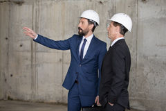 Professional architects in hard hats discussing project and looking away Royalty Free Stock Photo