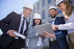 Professional architects in hard hats holding blueprint and using digital tablet Stock Photo