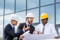 Professional architects in hardhats discussing blueprint outside modern building Stock Images