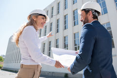 Professional architects in hardhats discussing blueprint while working at construction site Stock Photos