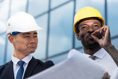 Professional architects in hardhats working with blueprint Stock Photo