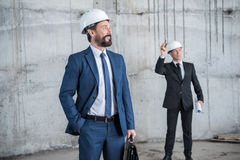 Professional architects in helmets discussing project at construction site Stock Photography