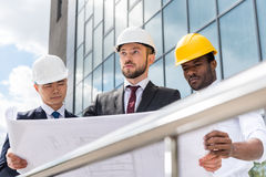 Professional architects in helmets working with blueprint outside modern building Royalty Free Stock Images