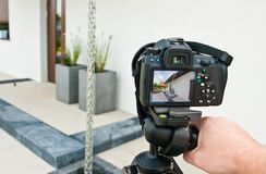 Shooting house exterior, photographer camera, tripod and ballhead. Professional architecture photographer tools: DSLR camera on tripod with modern flexible royalty free stock image