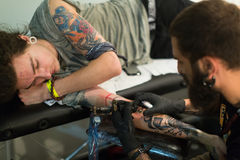 Professional artist  doing colorful tattoo on client arm Stock Photos