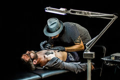 Professional artist doing colorful tattoo on client Royalty Free Stock Photos