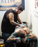 Professional artist  doing colorful tattoo on male  leg Stock Photography