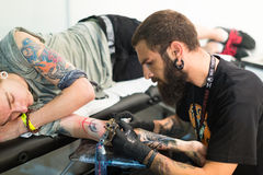 Professional artist  doing   tattoo on client arm Royalty Free Stock Photos