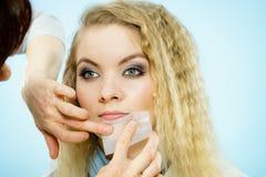 Woman using oil blotting tissues on model Stock Photos