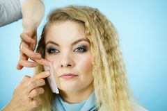 Woman using oil blotting tissues on model. Professional artist fixing fashion model make up using oil blotting tissues. Cosmetic objects, beauty treatment Royalty Free Stock Images