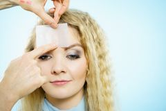 Woman using oil blotting tissues on model. Professional artist fixing fashion model make up using oil blotting tissues. Cosmetic objects, beauty treatment Royalty Free Stock Photo