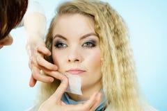 Woman using oil blotting tissues on model stock photography