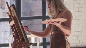 Professional artist inspired paints picture on canvas mounted on easel. In hands holds brush and palette, in background large light window and other works of stock video