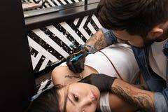 Professional artist making tattoo with machine stock photo