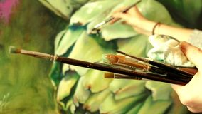 Professional artist painter holding brushes in her hand drawing an artwork. With oil paints - close-up 4K video stock video