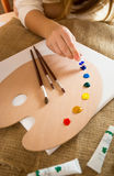 Professional artist squeezing oil paint from tubes on wooden pal Stock Photography